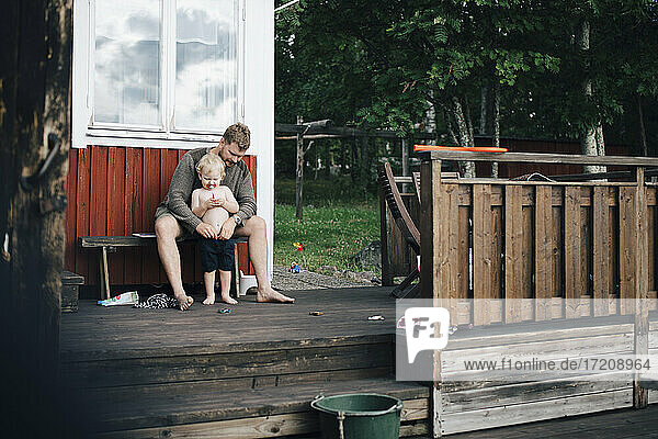 Father looking at son while sitting on bench during summer