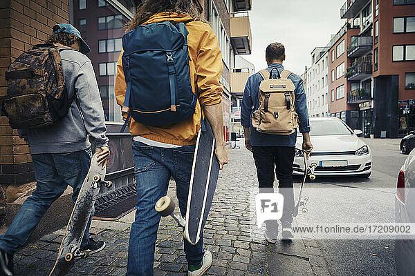 Rear view of male friends with skateboard walking on sidewalk in city