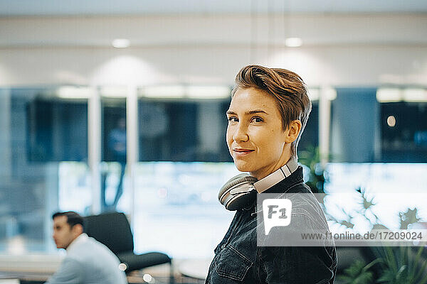 Portrait of short hair businesswoman with headphones around neck at office