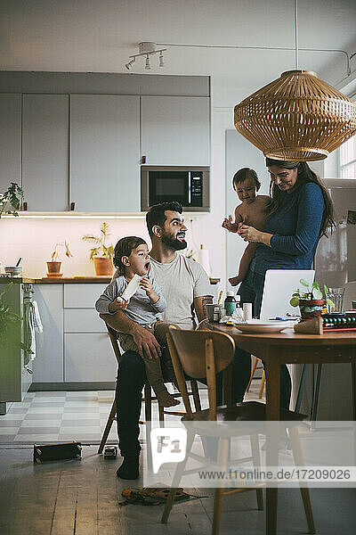 Smiling parents with children taking online consultation on video call in kitchen at home