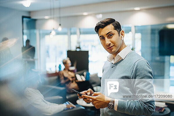 Portrait of businessman with smart phone while colleagues working in background at office