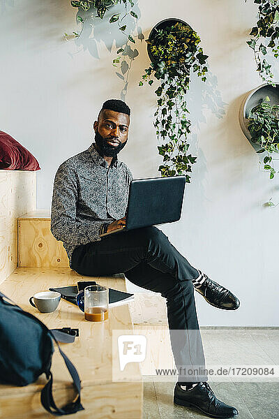 Portrait of businessman with laptop sitting on wooden seat in office