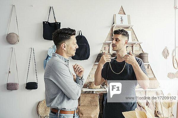 Male entrepreneur showing chain to customer in design studio