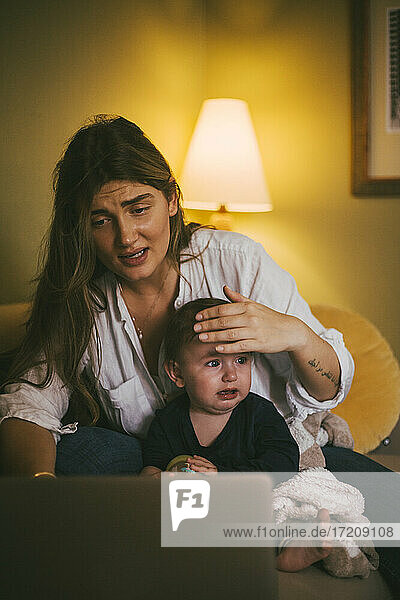 Mother with baby girl taking advice through video call on laptop at home