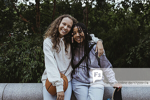 Portrait of smiling female friends with arm around sitting on retaining wall