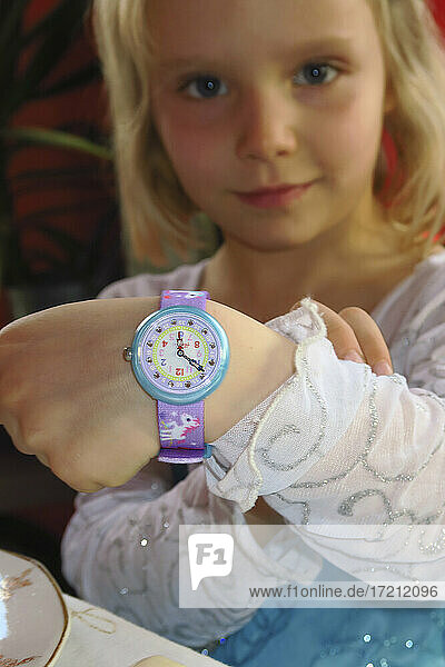 4-5 year old girl with her watch to learn the time