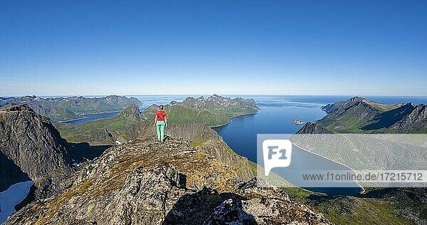 Wanderin steht am Gipfel des Grytetippen  Fjord und Berge  Senja  Norwegen  Europa