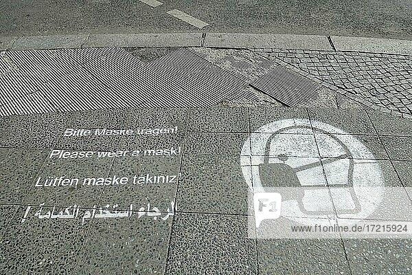 Maskenpflicht in 4 Sprachen  gesprüht auf einem Gehweg  Berlin  Deutschland  Europa