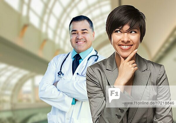 Happy mixed race woman looking to the side as hispanic male doctor stands behind her inside hospital
