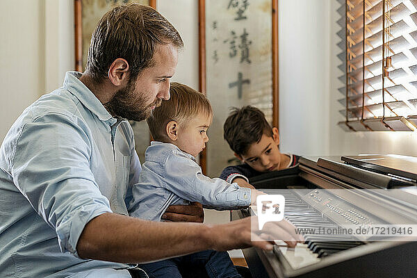 Father teaching piano to sons at home