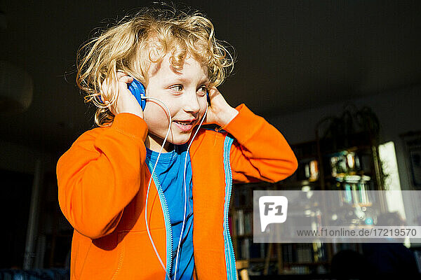 Blond boy looking away while listening music through headphones at home