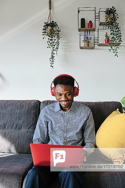 Smiling businessman with headphones using laptop while sitting at home