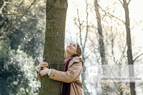 Smiling mid adult woman looking while embracing tree at park