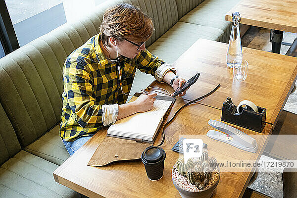 Male entrepreneur planning strategy while using smart phone sitting at desk in office