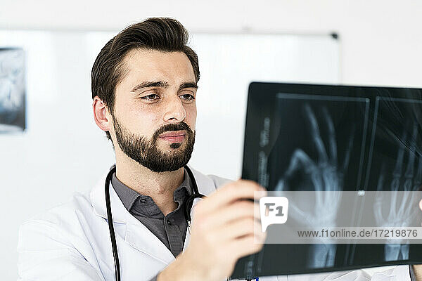 Handsome male healthcare worker examining x-ray