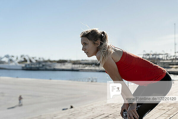 Thoughtful female jogger resting on pier