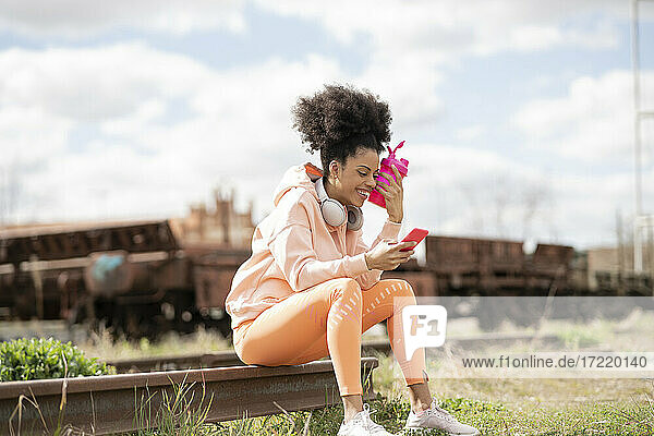 Woman with shaker using smart phone while sitting on railway track in shunting yard