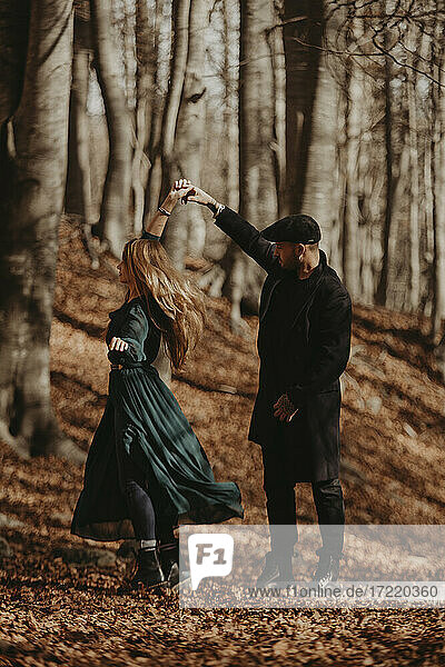 Couple dancing in forest during autumn
