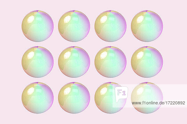 Three dimensional pattern of rows of bubbles against pink background