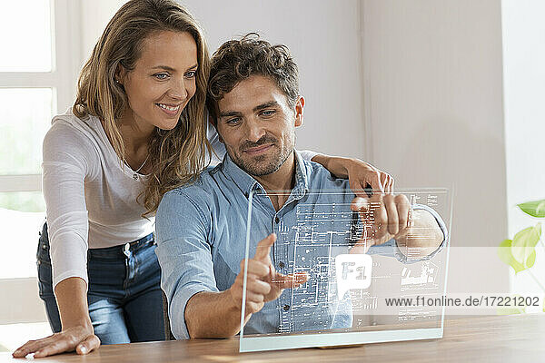 Mid adult couple looking at floor plan over transparent screen at home