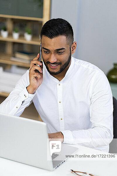Männlicher Unternehmer  der mit seinem Smartphone spricht  während er einen Laptop im Büro benutzt