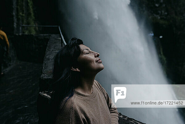 Woman with eyes closed relaxing at waterfall