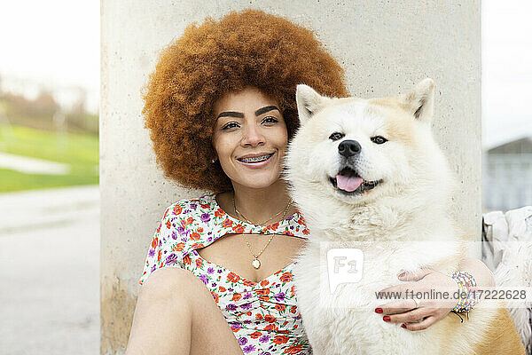 Redhead woman smiling while sitting with dog in front of pillar