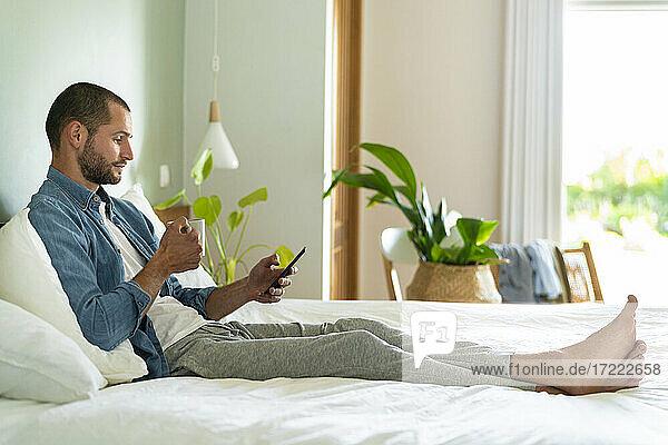 Junger Mann mit Kaffeetasse und Smartphone zu Hause