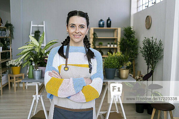 Female gardener with arms crossed standing in workshop