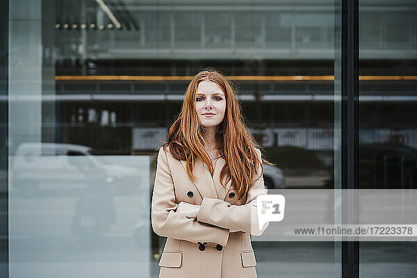 Confident redhead woman with arms crossed standing in front of glass