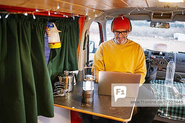 Smiling mature man using laptop in motor home