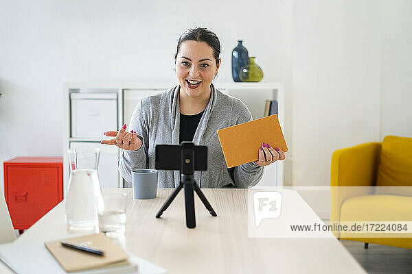 Female freelancer explaining during video conference through smart phone at home office