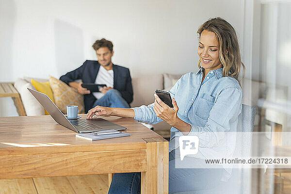 Lächelnde Frau mit Laptop auf dem Tisch  die ihr Smartphone hält  während ihr Freund zu Hause im Büro sitzt
