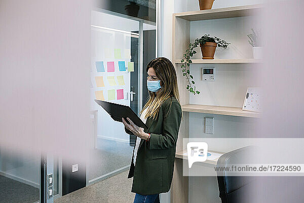 Businesswoman wearing protective face mask holding clipboard while standing at office
