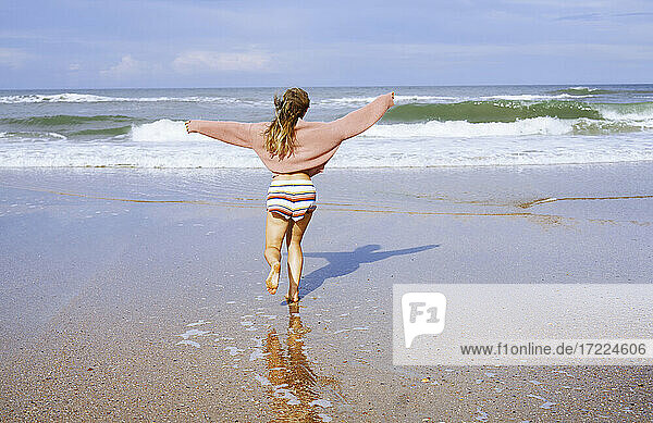Teenage girl running on beach toward ocean