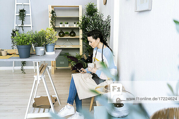 Woman with mug using smart phone while sitting in workshop