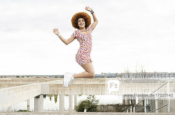 Playful woman in floral dress jumping with hands raised in park