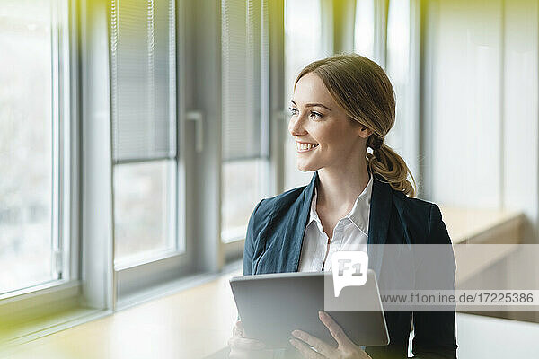 Happy businesswoman looking away while holding digital tablet in office