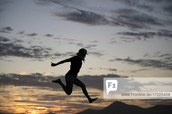 Excited woman jumping during sunset