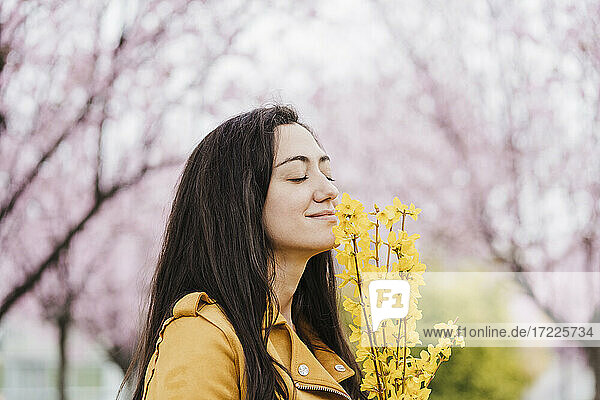 Smiling woman with eyes closed smelling fragrance of yellow flowers