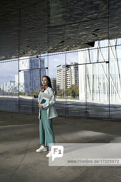 Female entrepreneur standing in front of glass office building