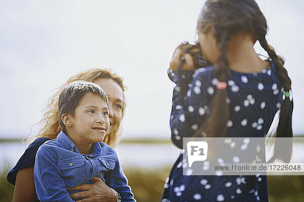 Girl photographing mother and brother