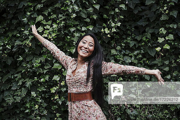 Cheerful woman with arms outstretched standing by plants in public park