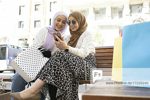 Young Arab woman using smart phone by female friend sitting on bench in city