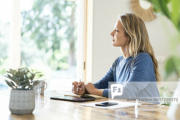 Blond businesswoman writing in diary while sitting at table