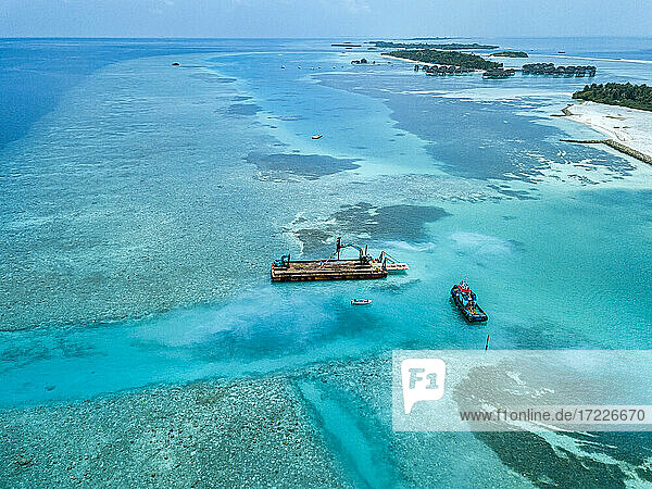 Aerial view of earth movers handling poles on floating platform in Male Atoll