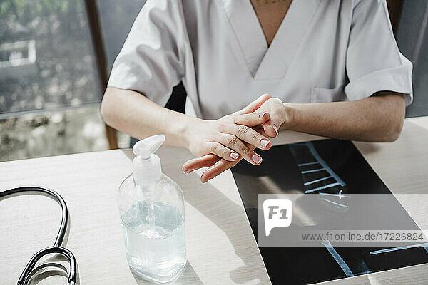 Female doctor rubbing hands together while applying sanitiser at desk