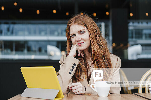 Beautiful woman sitting in front of digital tablet at cafe