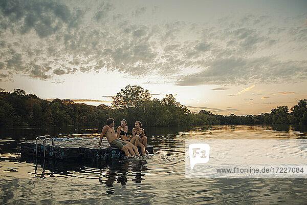 Freunde  die sich am See vergnügen  auf einer Badeplattform sitzend Freunde, die sich am See vergnügen, auf einer Badeplattform sitzend