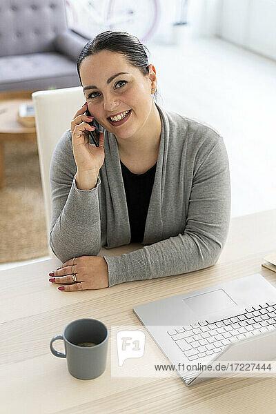 Lächelnde Geschäftsfrau  die bei der Arbeit zu Hause ein Mobiltelefon benutzt